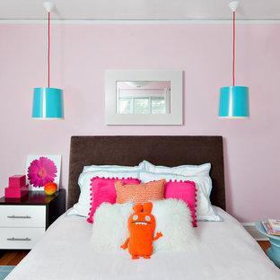 Example of a trendy medium tone wood floor bedroom design in New York with pink walls