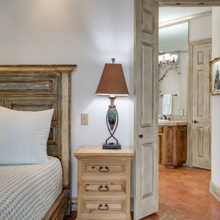 Transitional master bedroom in Dallas with terra-cotta floors.