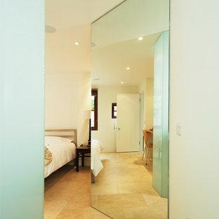 На фото: с высоким бюджетом большие хозяйские спальни в стиле модернизм с белыми стенами и полом из известняка