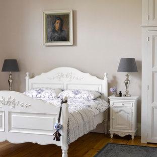 Ornate Medium Tone Wood Floor Bedroom Photo In Hertfordshire With Beige Walls