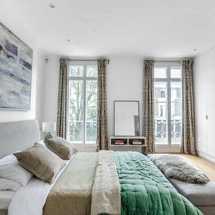 This is an example of a medium sized contemporary master bedroom in London with grey walls, light hardwood flooring, no fireplace and beige floors.