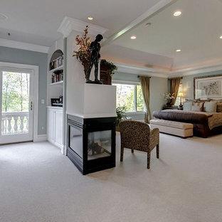 Diseño de dormitorio principal, tradicional, extra grande, con paredes marrones, moqueta, chimenea de doble cara, marco de chimenea de metal y suelo blanco