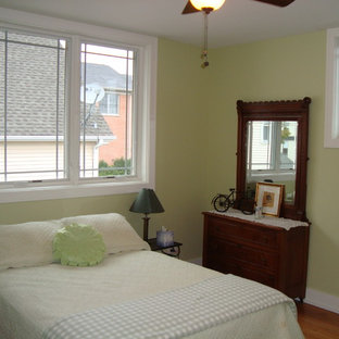 Example of a small transitional medium tone wood floor bedroom design in Chicago with green walls
