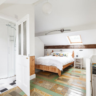 Example of an eclectic painted wood floor and multicolored floor bedroom design in Manchester with white walls