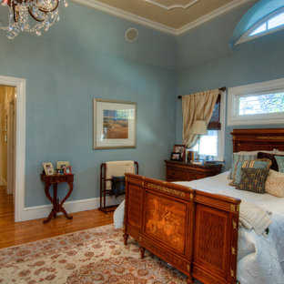 Modelo de dormitorio principal, clásico, de tamaño medio, sin chimenea, con paredes azules, suelo de madera clara y suelo azul