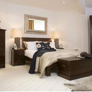 Esempio di una camera degli ospiti tropicale di medie dimensioni con pareti bianche e pavimento in legno verniciato