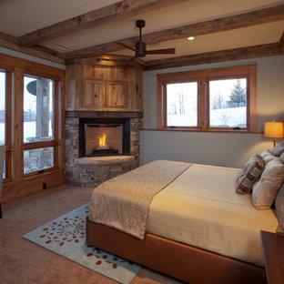 Imagen de habitación de invitados rústica, de tamaño medio, con chimenea de esquina, marco de chimenea de piedra, paredes blancas y moqueta