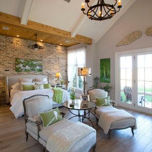 ダラスの広いカントリー風おしゃれな主寝室 (グレーの壁、淡色無垢フローリング、標準型暖炉、レンガの暖炉まわり、茶色い床) のレイアウト