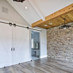 Modelo de dormitorio principal, minimalista, grande, con paredes grises, suelo de madera clara, chimenea tradicional y marco de chimenea de ladrillo