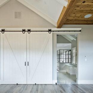 Imagen de dormitorio principal, minimalista, grande, con paredes grises, suelo de madera clara, chimenea tradicional y marco de chimenea de ladrillo