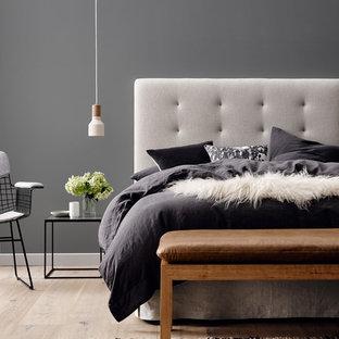Modelo de dormitorio minimalista con paredes grises y suelo de madera clara