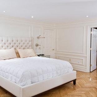 Inredning av ett klassiskt stort huvudsovrum, med vita väggar, mellanmörkt trägolv, brunt golv, en standard öppen spis och en spiselkrans i trä