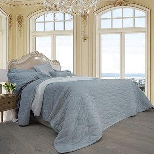 Diseño de dormitorio principal, mediterráneo, con paredes azules, suelo de madera pintada, chimenea de esquina, marco de chimenea de madera y suelo turquesa