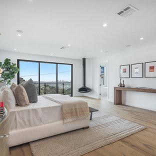 ロサンゼルスの巨大なミッドセンチュリースタイルのおしゃれな主寝室 (吊り下げ式暖炉、白い壁、淡色無垢フローリング、茶色い床)