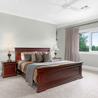 Large traditional master bedroom in Sydney with green walls, carpet and no fireplace.