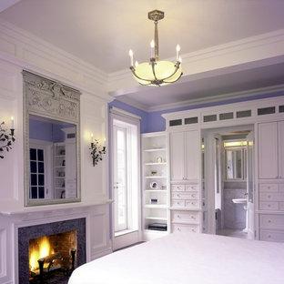 Diseño de dormitorio principal, clásico renovado, grande, con paredes azules, suelo de madera en tonos medios, chimenea tradicional y marco de chimenea de piedra