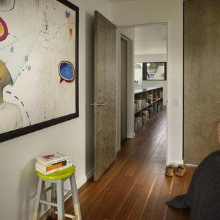 Small minimalist medium tone wood floor bedroom photo in Seattle with white walls
