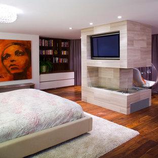 Foto di una camera matrimoniale contemporanea con pavimento in legno massello medio e camino bifacciale