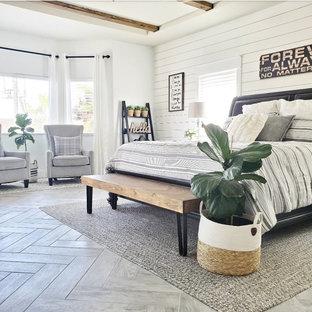 Country Hauptschlafzimmer mit weißer Wandfarbe, Keramikboden, Kamin, Kaminumrandung aus Holzdielen, grauem Boden, freigelegten Dachbalken und Holzdielenwänden in Las Vegas