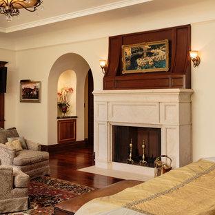 Idee per un'ampia camera matrimoniale mediterranea con pareti beige, parquet scuro, camino classico e cornice del camino in pietra