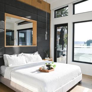 Modernes Hauptschlafzimmer mit weißer Wandfarbe, hellem Holzboden und Wandpaneelen in Vancouver