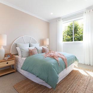 Ejemplo de habitación de invitados tropical, de tamaño medio, con paredes rosas, moqueta y suelo beige