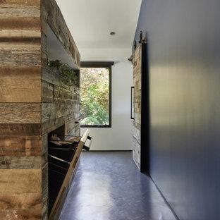 На фото: большая хозяйская спальня в стиле ретро с синими стенами, бетонным полом, стандартным камином, фасадом камина из штукатурки и серым полом с