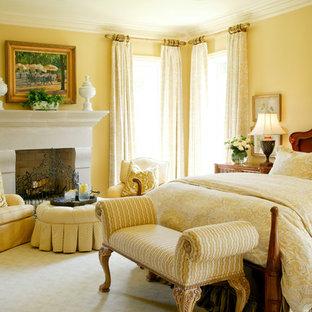 Exempel på ett klassiskt sovrum, med gula väggar, heltäckningsmatta och en standard öppen spis