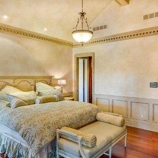 デトロイトの大きいトラディショナルスタイルのおしゃれな主寝室 (ベージュの壁、無垢フローリング、両方向型暖炉、漆喰の暖炉まわり、茶色い床) のインテリア
