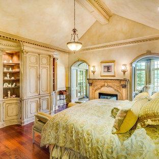 Esempio di una grande camera matrimoniale tradizionale con pareti beige, pavimento in legno massello medio, camino bifacciale, cornice del camino in intonaco e pavimento marrone