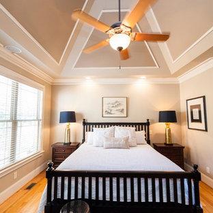 Idées déco pour une chambre parentale craftsman de taille moyenne avec un mur beige et un sol en bois clair.