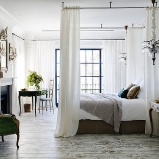 Design ideas for a mid-sized transitional master bedroom in Sydney with white walls, medium hardwood floors, a standard fireplace and grey floor.