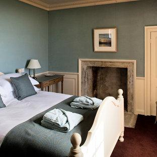 Ejemplo de habitación de invitados clásica, pequeña, con paredes azules, moqueta, chimenea tradicional y marco de chimenea de piedra