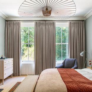 Classic bedroom in London with green walls, medium hardwood flooring and brown floors.
