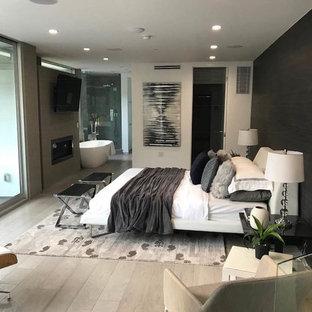 Diseño de dormitorio principal, moderno, de tamaño medio, con paredes blancas, suelo de madera clara, marco de chimenea de hormigón y suelo beige