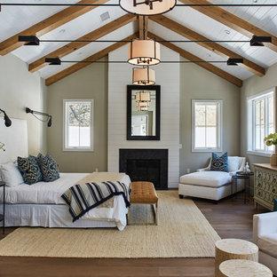 Klassisches Hauptschlafzimmer mit grauer Wandfarbe, braunem Holzboden und Kamin in Los Angeles