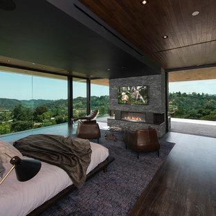 Modelo de dormitorio actual con paredes marrones, suelo de madera oscura, chimenea lineal, marco de chimenea de piedra y suelo marrón