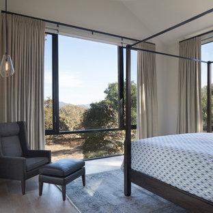 Diseño de habitación de invitados minimalista, de tamaño medio, con paredes amarillas, suelo de madera clara y suelo beige