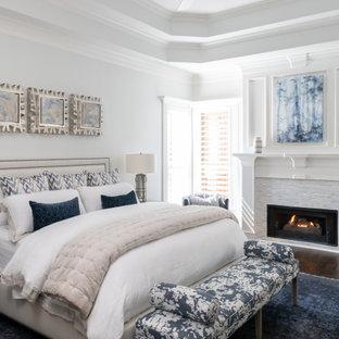 ダラスのトランジショナルスタイルのおしゃれな主寝室 (濃色無垢フローリング、標準型暖炉、石材の暖炉まわり、折り上げ天井) のインテリア