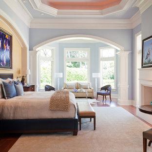 Imagen de dormitorio principal, tradicional, extra grande, con paredes azules, suelo de madera en tonos medios, chimenea tradicional, marco de chimenea de madera y suelo marrón