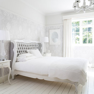 Photo of a mid-sized shabby-chic style bedroom in Sussex with painted wood floors, white floor, multi-coloured walls and no fireplace.