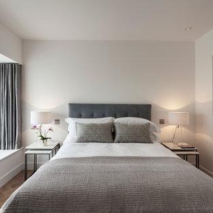 Ejemplo de habitación de invitados moderna, de tamaño medio, con paredes blancas, suelo de madera en tonos medios y suelo beige