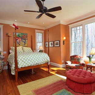 Photo of an arts and crafts bedroom in Raleigh with orange walls, medium hardwood floors and no fireplace.