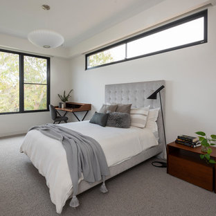 This is an example of a contemporary guest bedroom in Melbourne with white walls, carpet and multi-coloured floor.