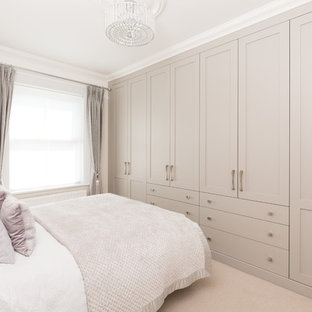 Inspiration for a large transitional master bedroom in Hampshire with beige walls, carpet and beige floor.