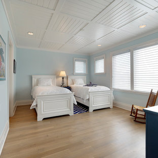 Large beach style guest light wood floor and brown floor bedroom photo in Wilmington with blue walls and no fireplace