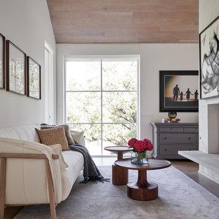 Idee per una camera matrimoniale classica di medie dimensioni con pareti bianche, pavimento in legno massello medio, pavimento marrone, camino bifacciale e cornice del camino piastrellata