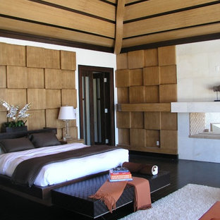 Ejemplo de dormitorio exótico con paredes blancas, suelo de madera oscura y suelo negro