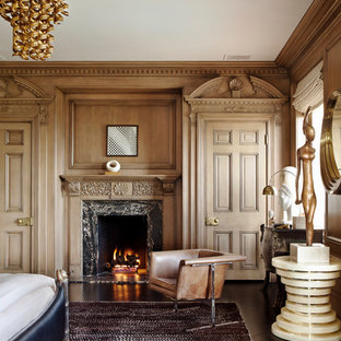 Eclectic master dark wood floor bedroom photo in Los Angeles with brown walls, a standard fireplace and a stone fireplace