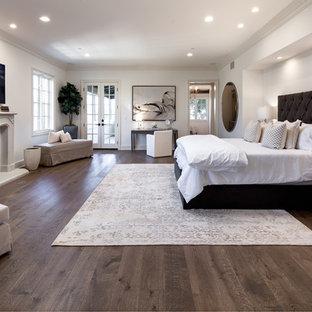 Modelo de dormitorio principal, mediterráneo, con suelo de madera oscura, marco de chimenea de hormigón y suelo marrón